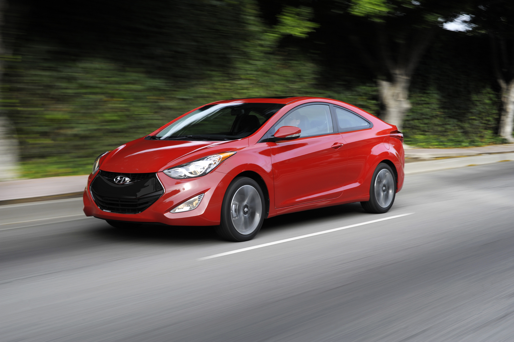 Manufacturer photo: Hyundai's signature hexagonal front fascia opening and jeweled swept-back headlights give the 2013 Elantra Coupe a lean, aggressive demeanor