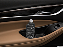 2018 Buick Enclave Essence, second row side cup holder with coffee prop, or second row door cup holder with water bottle.